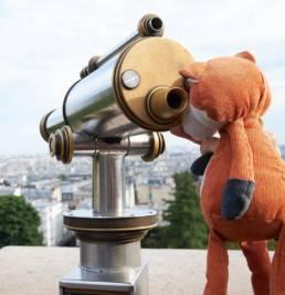 Mascotte de Foxtrail Paris qui regarde a travers un telescope