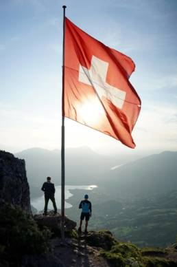 Swiss flag on a mountain with lake in background